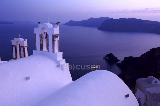 Cloche de l'église et vue sur la mer au crépuscule, Santorin, Grèce — Photo de stock
