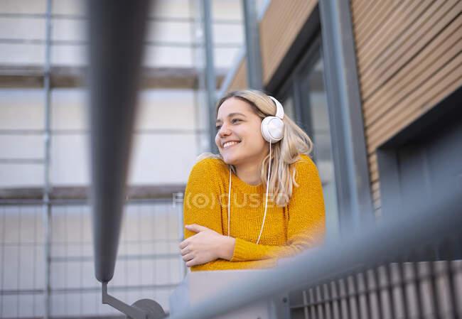 Mujer joven y feliz escuchando música con auriculares - foto de stock