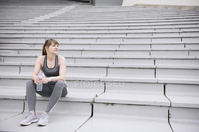 Молодая женщина в спортивной одежде сидит на бетонных трибунах с бутылкой воды — стоковое фото