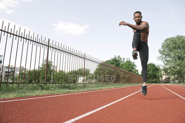 Homme athlétique pris dans les airs tout en sautant sur l'hippodrome en caoutchouc — Photo de stock