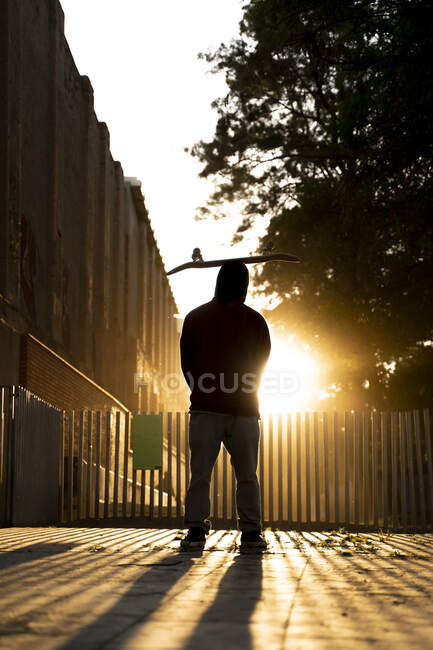 Back view of skater standing at backlight with skateboard on his head — Stock Photo