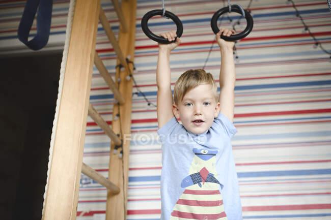 Портрет хлопчика, що висить на гімнастичних кільцях. — стокове фото