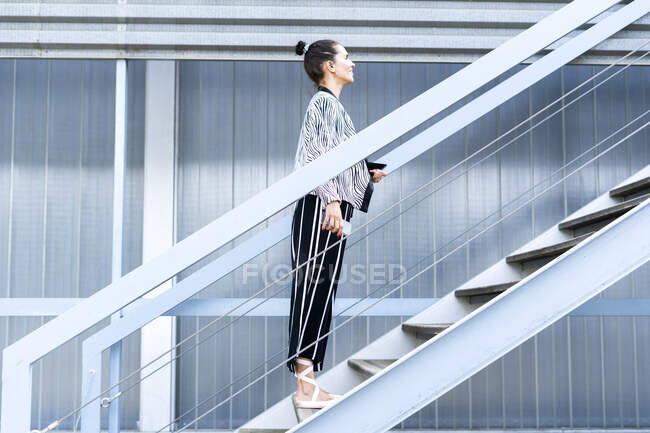 Female ballet dancer with smartphone and tablet standing on steps — Stock Photo
