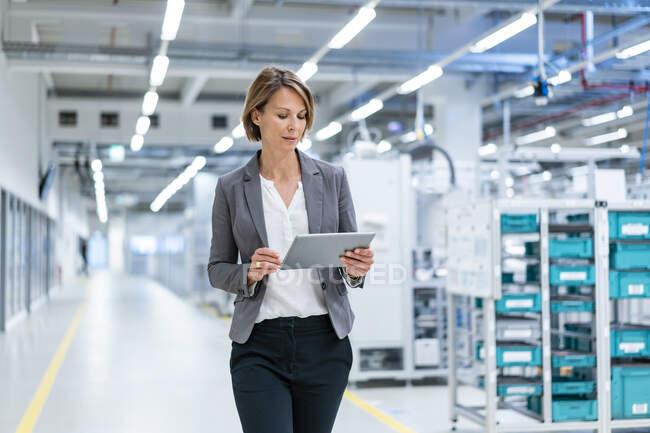 Mujer de negocios con tableta en una fábrica moderna - foto de stock