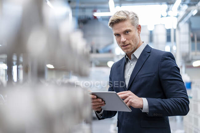 Portrait of businessman with tablet in a modern factory — Stock Photo