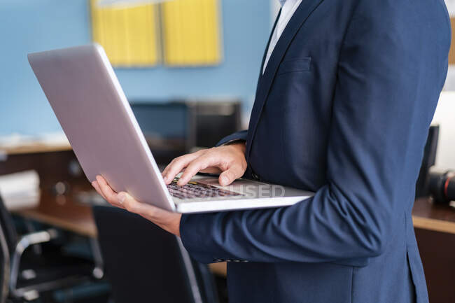 Close-up of businessman using laptop in office — Stock Photo