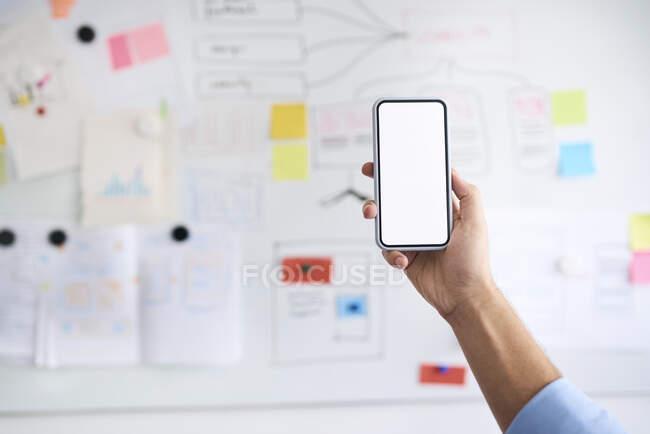 Mano masculina sosteniendo en alto un teléfono inteligente frente a una pizarra blanca - foto de stock