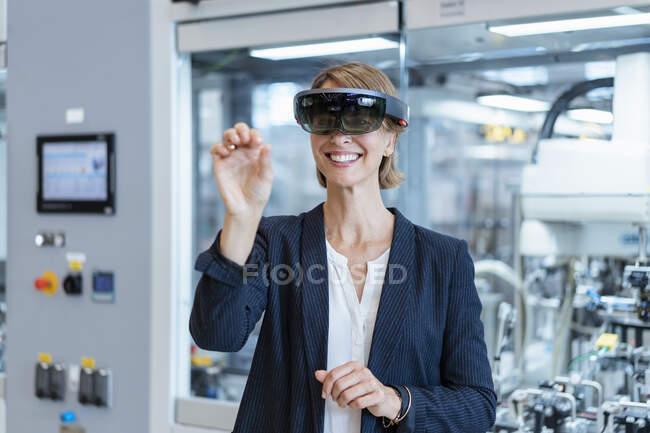 Mujer de negocios sonriente con gafas AR en una fábrica moderna - foto de stock