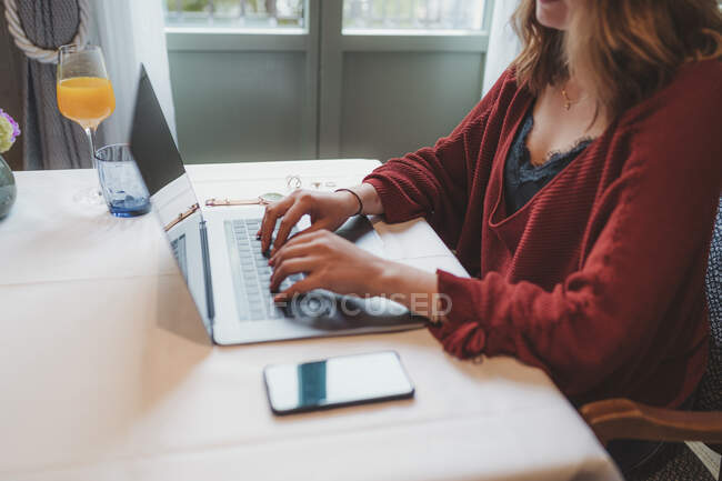 Gros plan de la femme utilisant un ordinateur portable sur la table dans un café — Photo de stock