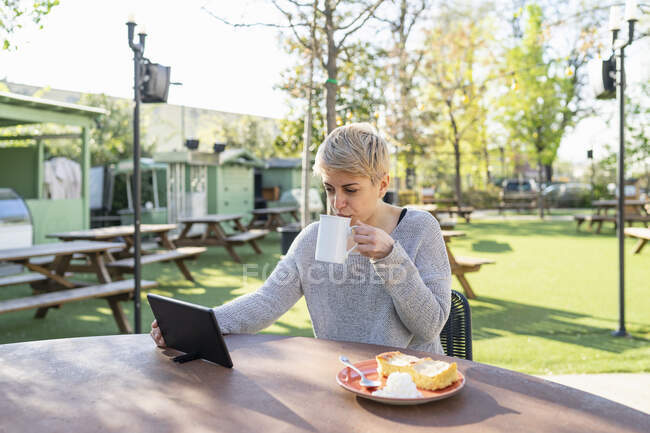Mujer joven bebiendo taza de café al aire libre mientras usa la tableta digital - foto de stock