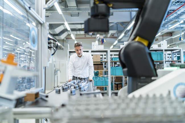 Бізнесмен у сучасному заводському залі дивиться на робота. — стокове фото