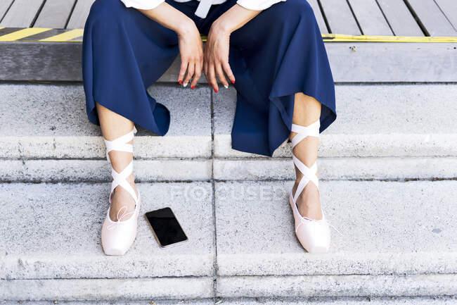 Dançarina feminina com sapatos de dedo do pé sentado em passos — Fotografia de Stock