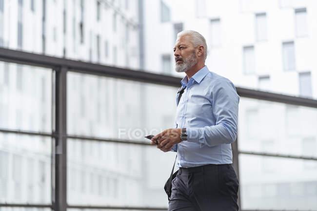 Зрілий бізнесмен з мобільним телефоном. — стокове фото