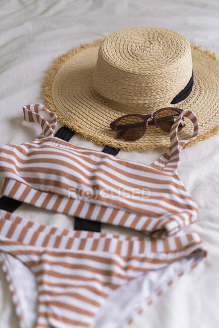 Bikini and straw hat lying on bed — Stock Photo