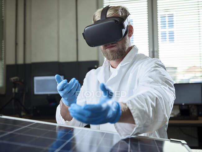 Техник с VR очками и солнечной панелью в лаборатории — стоковое фото