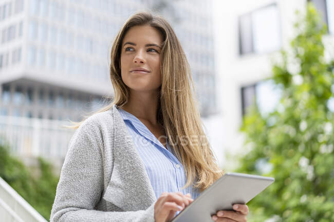Portrait of young businesswoman using tablet, office buildings in the background — Stock Photo