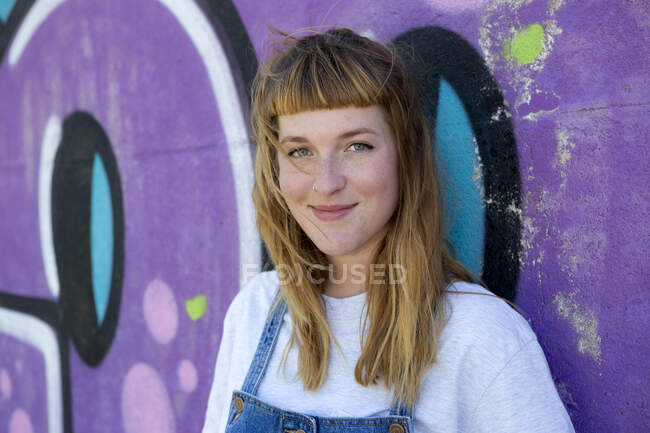 Young woman in front of purple graffiti — Stock Photo