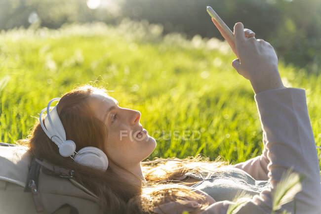 Молода руда жінка з навушниками і смартфоном у парку. — стокове фото