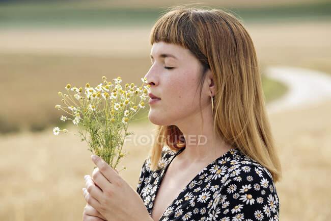 Giovane donna con gli occhi chiusi mazzo profumato di fiore di camomilla — Foto stock