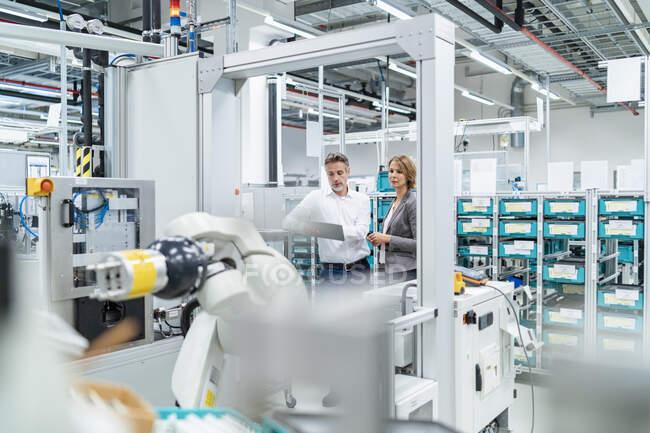 Businesswoman y manwith tableta hablando en una fábrica moderna - foto de stock