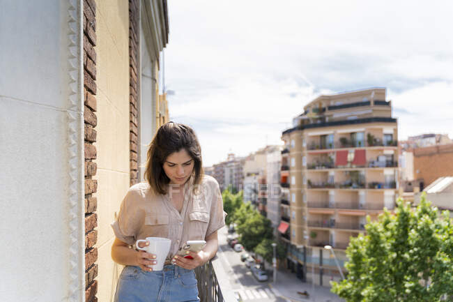 Young woman on balcony in the city using cell phone — Stock Photo