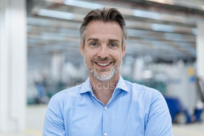 Портрет усміхненого бізнесмена з фабричного залу. — стокове фото