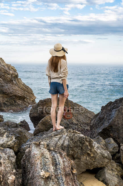 Back view of young woman with ukulele standing on rock looking at the sea — Stock Photo