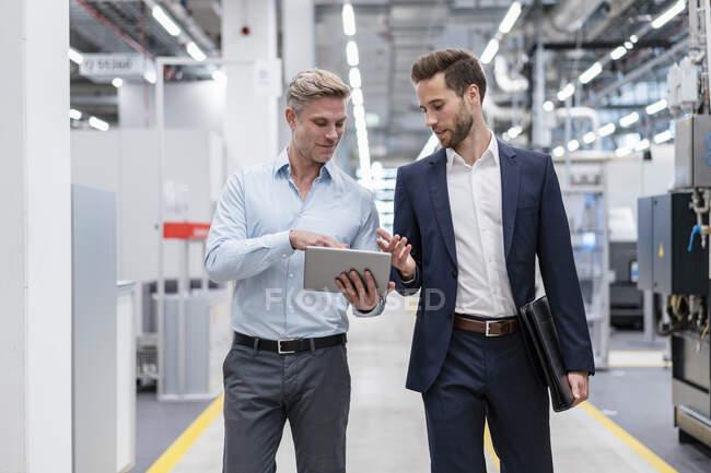 Zwei Geschäftsleute mit Tablet im Gespräch in einer modernen Fabrik — Stockfoto