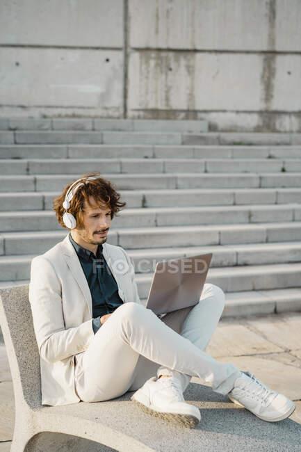 Бізнесмен з навушниками працює на ноутбуку на відкритому повітрі. — стокове фото