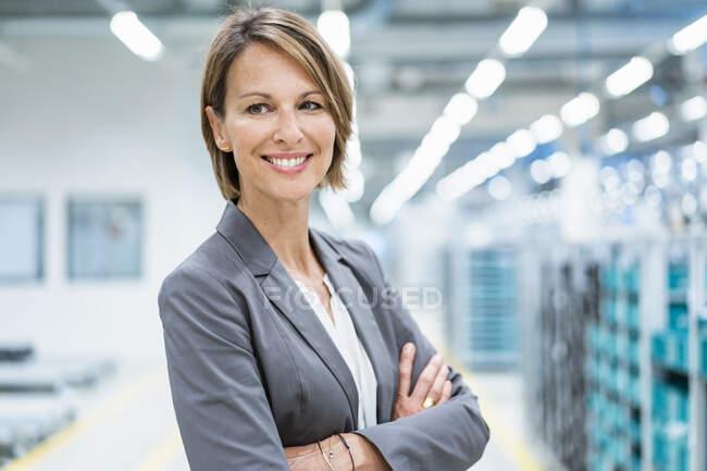 Retrato de una mujer de negocios sonriente en una fábrica moderna - foto de stock