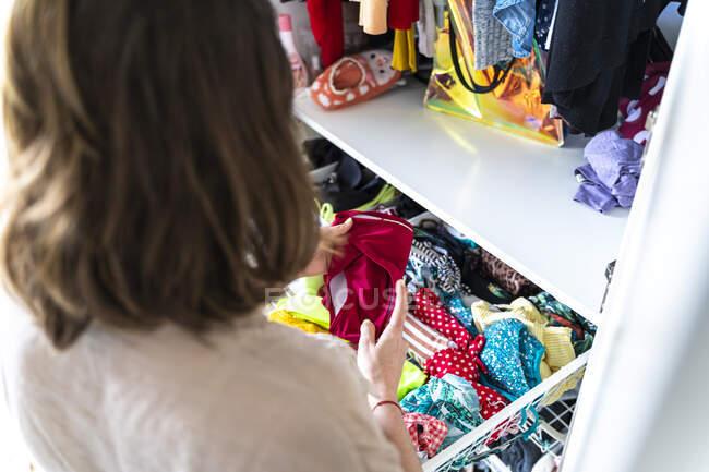 Женщина убирает свой гардероб — стоковое фото