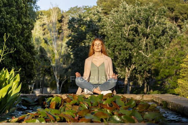 Молодая рыжая женщина медитирует в парке — стоковое фото