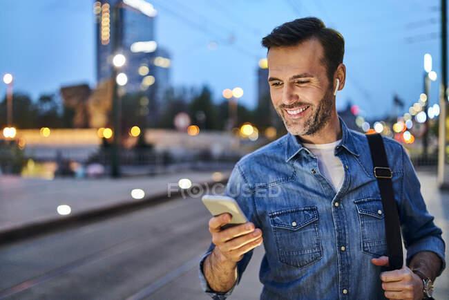 Uomo in piedi con smartphone in attesa di pendolare la sera dopo il lavoro — Foto stock