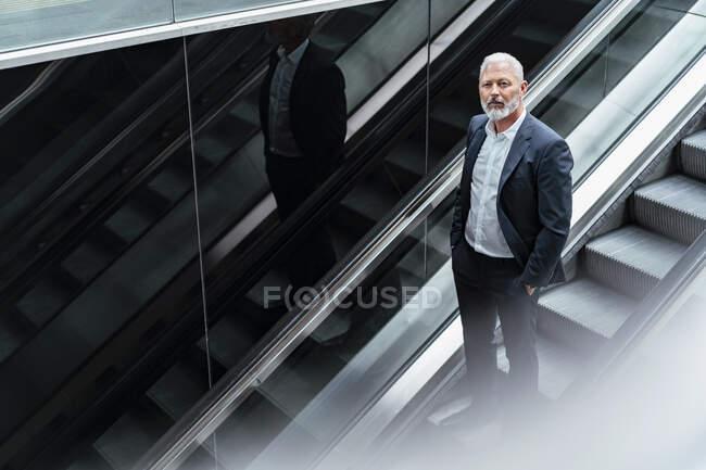 Homme d'affaires mature sur un escalator — Photo de stock