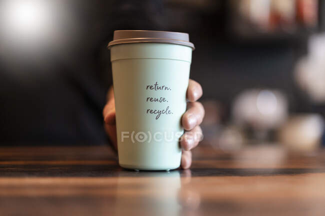 Hand holding deposit cup for Coffee to go, close-up — Stock Photo