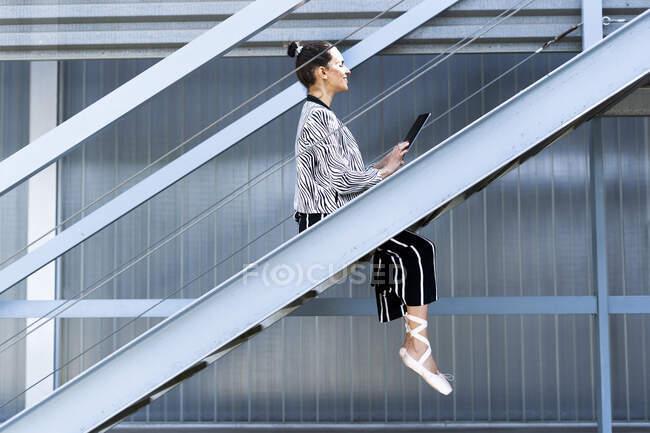 Female ballet dancer using tablet on steps — Stock Photo
