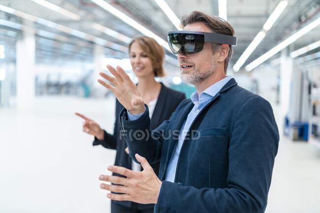 Empresario con gafas AR y mujer de negocios en una sala de fábrica - foto de stock