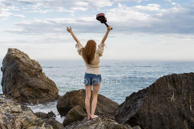 Rückansicht einer jungen Frau mit Ukulele, die auf einem Felsen steht und aufs Meer blickt — Stockfoto