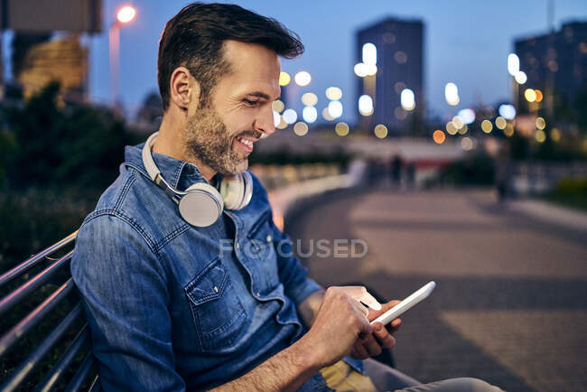 Smiling man using his smartphone while sitting on a bench in the evening — Stock Photo
