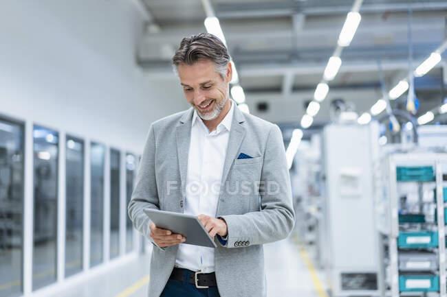 Hombre de negocios sonriente usando tableta en una fábrica moderna - foto de stock