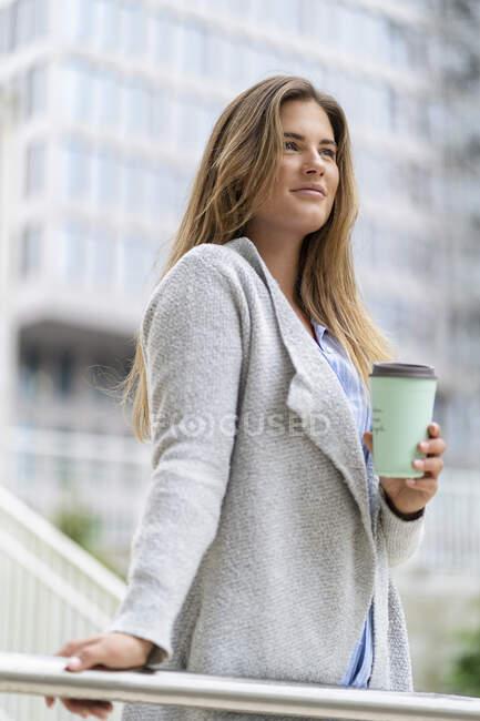 Jeune femme d'affaires avec café pour aller tasse, immeuble de bureaux en arrière-plan — Photo de stock