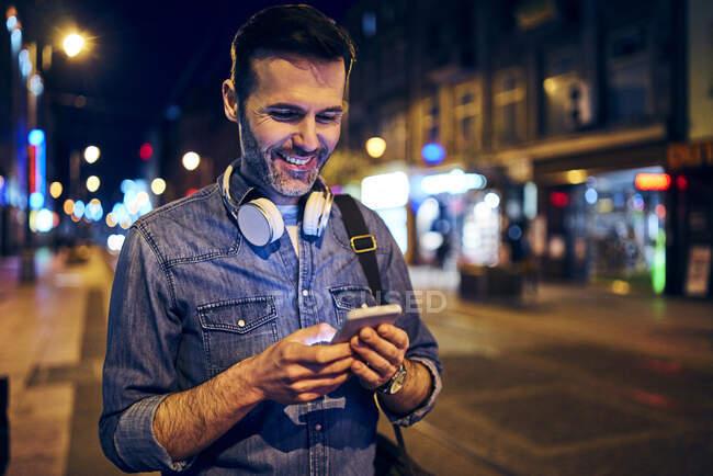 Усміхнений чоловік вночі користується своїм смартфоном у місті, чекаючи трамвая. — стокове фото