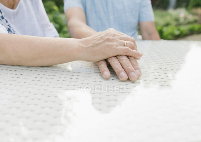 Senior couple sitting at garden table holding hands, close-up — Stock Photo
