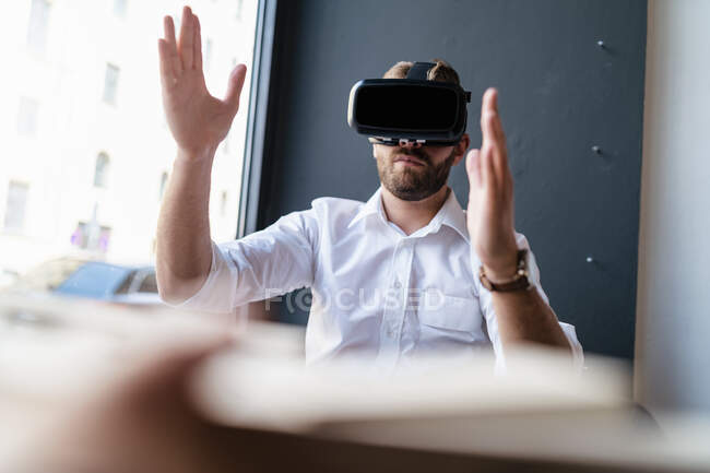 Businessman with architectural model in office wearing VR glasses — Stock Photo