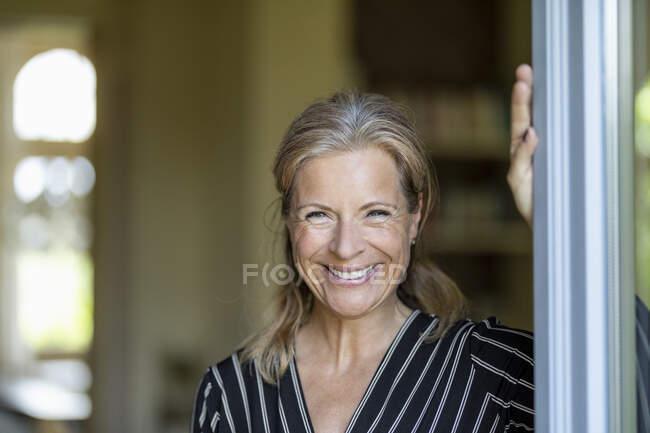 Retrato de mujer madura sonriente de pie en la puerta de la terraza abierta - foto de stock