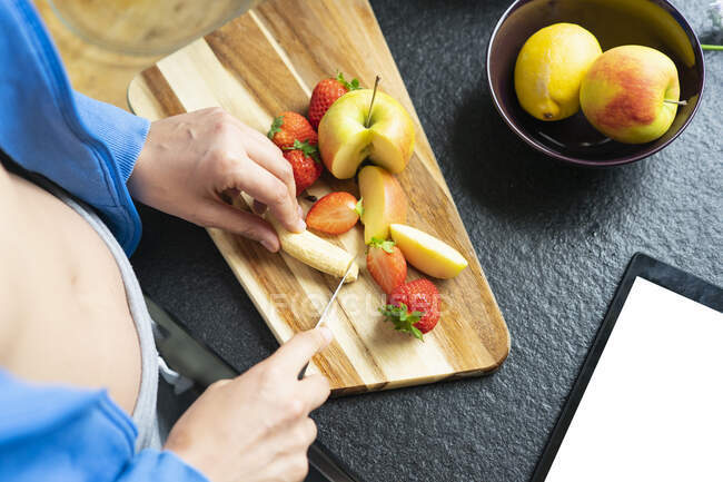 Woman chopping fruits in her kitchen, close up — Stock Photo