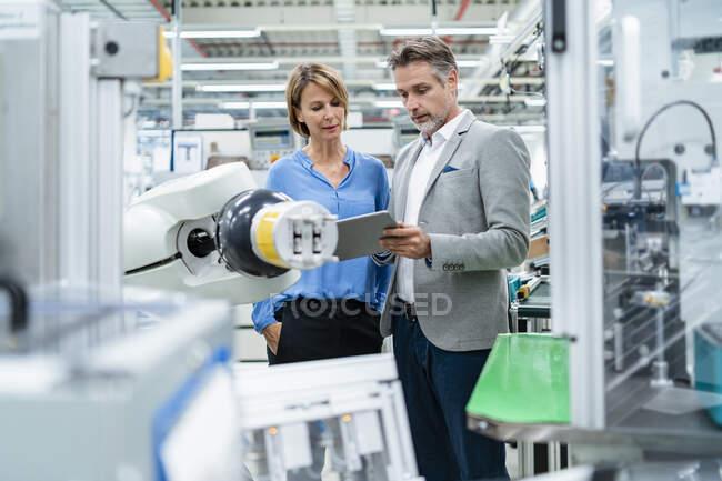 Empresario con tableta y mujer hablando en robot de montaje en una fábrica - foto de stock