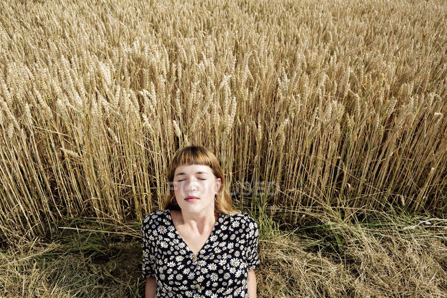 Portrait of young woman with eyes closed relaxing in front of grain field — Stock Photo