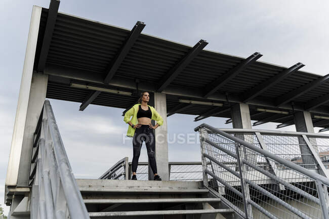 Sporty woman standing on grandstand, looking at distance — Stock Photo