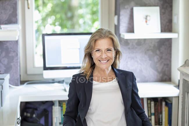 Retrato de mujer de negocios madura sonriente en la oficina en casa - foto de stock